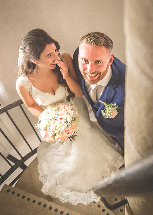 bride and groom on stairwell laughing
