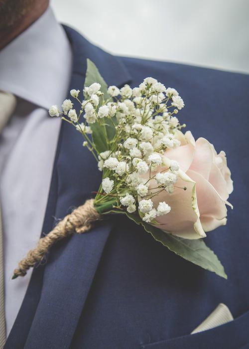 buttonhole pink flower blue suit