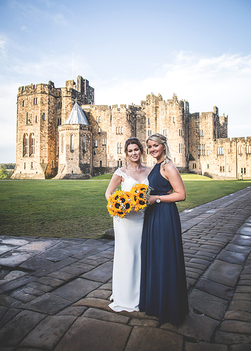 bride and bridesmaid in front of alnwick castle blue sky