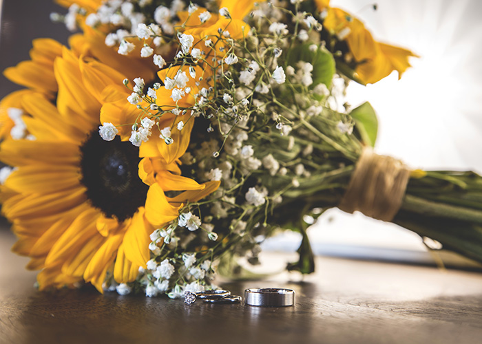 wedding rings with sunflower bouquets