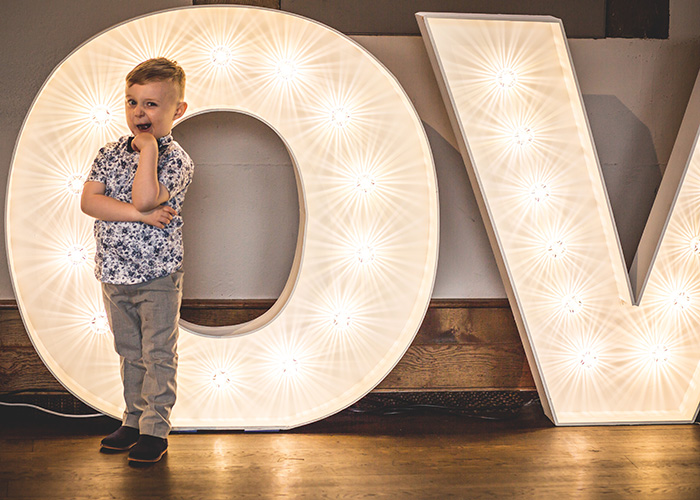 little boy standing in front of wedding light up letters