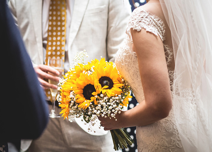 bride with stunning yellow sunflower bouquet