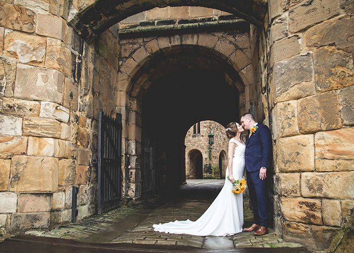 bride and groom in archway alnwick castle