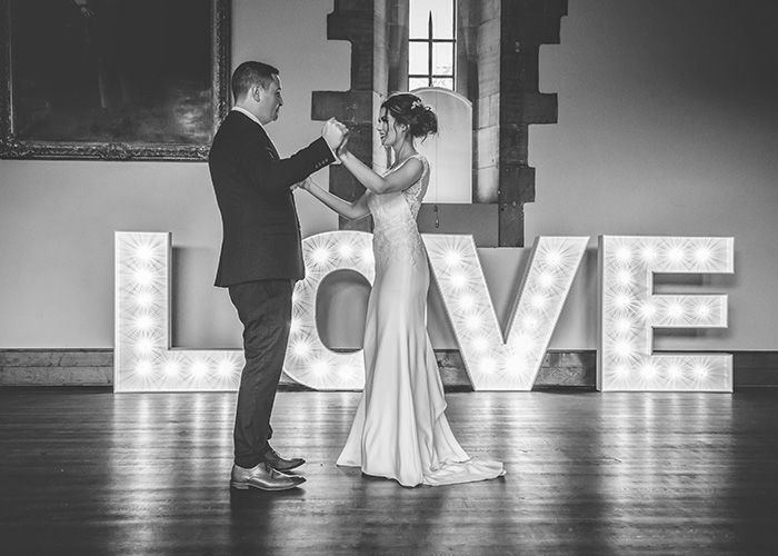 first dance in front of lit up letters