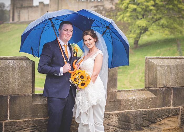 bride and groom with umbreallas on bridge