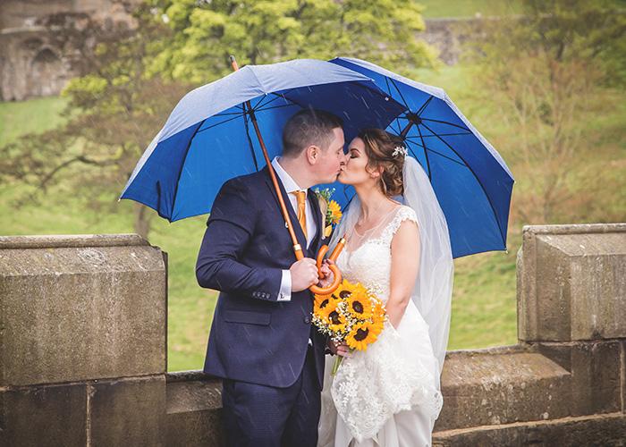 bride and groom in rain with blue umbrellas